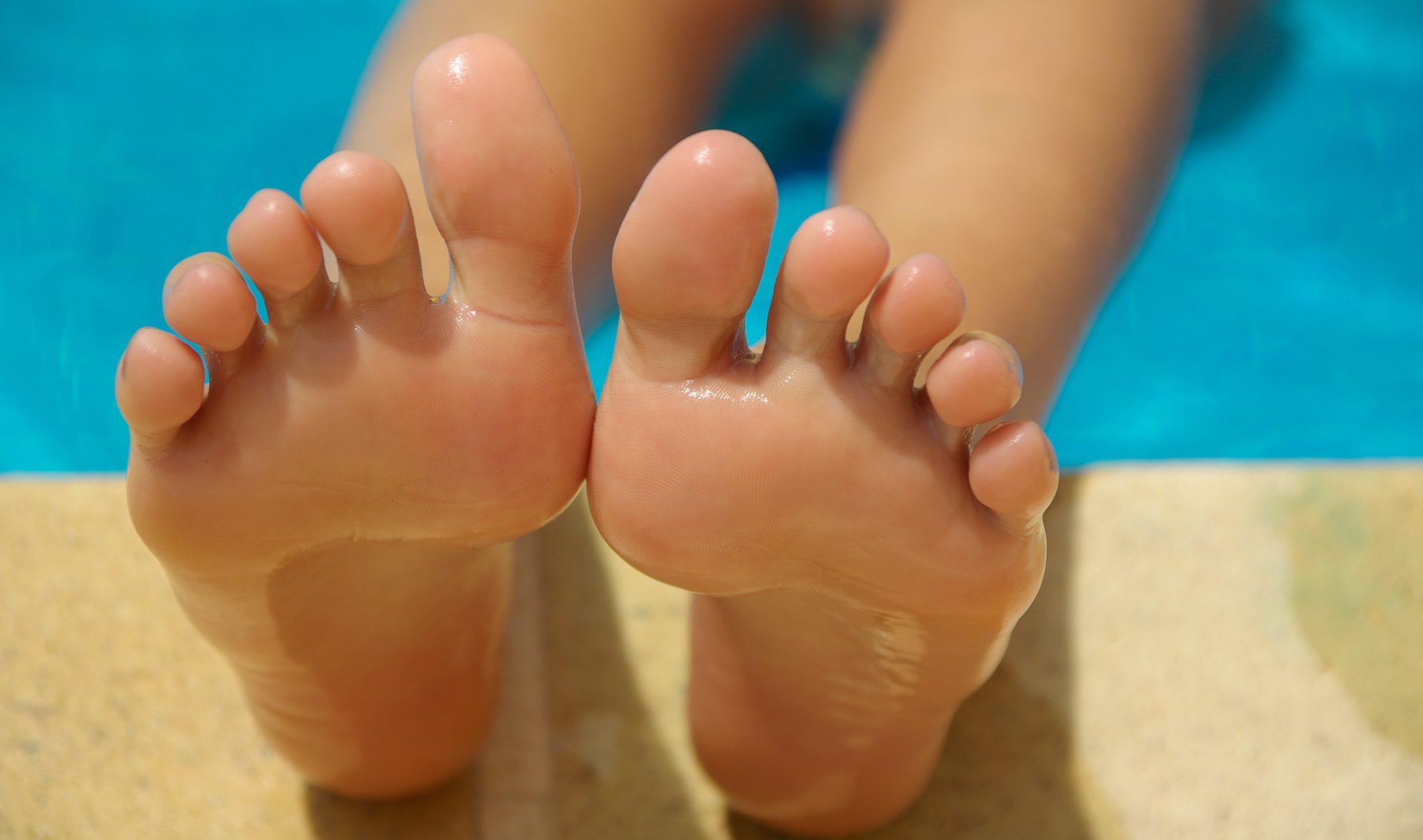 bosé nohy opřené o kamenný okraj bazénu. Osoba je ponořena do vody, ale nelze ji vidět. Na fotce jsou zobrazeny jen chodidla a část lýtek