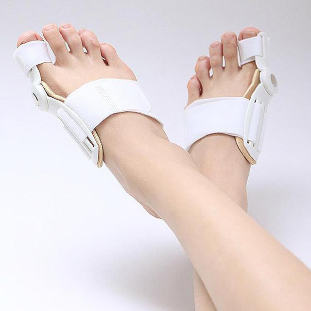 Dvě překročené nohy přes sebe. Jde vidět jen chodidla a holeně. Na chodidlech jsou korektory vbočeného palce v bílé barvě.