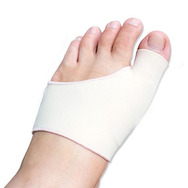 Korektor vbočeného palce na chodidle obepínající palec u nohy a nárt. Korektor je v bílé barvě.